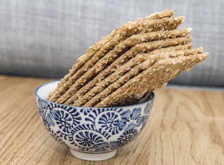 Side view of bio delicious crispbread bread in japanese blue porcelain bowl on wooden oak table
