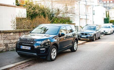 Strasbourg, France - Feb 13 2017: New luxury Land Rover Discovery executive SUV parked on a French street with multiple cars parked in background