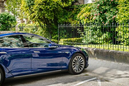 Strasbourg, France - May 19, 2016: Front view of modern luxury Tesla Model S 90D electric supercar in beautiful blue color parked on the French street near luxury garden Redakční