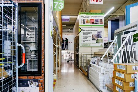 Paris, France - Feb 4, 2019: DIY store with multiple selection of wooden bars f, cardboards with tools, plastic windows and workers installing newest accessory in background