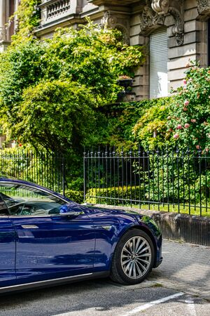 Strasbourg, France - May 19, 2016: Modern luxury Tesla Model S 90D electric supercar in beautiful blue color parked on the French street near beautiful French architecture building