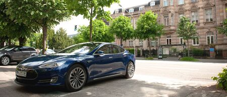 Strasbourg, France - May 19, 2016: New modern luxury Tesla Model S 90D electric supercar in beautiful blue color parked on the French street with beautiful Haussmannian architecture buildings in background