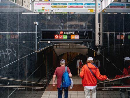 Barcelona, Spain - Jun 2, 2018: Adult couple descending stairs of the TMB Espanya metro underground station with L1, L3, L8 access Redakční