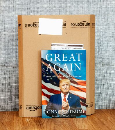Strasbourg, France - Feb 12 2017: Great Again how to fix our crippled America book by Donald Trump, United States President with Amazon Cardboard box - unpacking of new internet Shopping