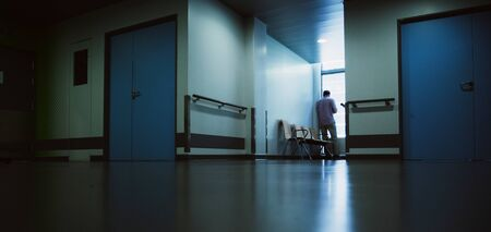 Lonely patient in full length in modern hospital waiting lobby room near the window as he waits for good or bad news from his doctor - blue hospital atmosphere Banque d'images
