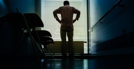 Lonely patient in full length in modern hospital waiting lobby room near the window as he waits for good or bad news from his doctor - rear view
