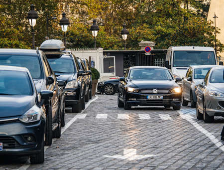 Paris, France - Oct 13, 2018: Cars parking in a row at Depose Minute short time parking at the entrance of Gare de Est in Paris, France with black Volkswagen passat car driving whti turned on headlights Éditoriale