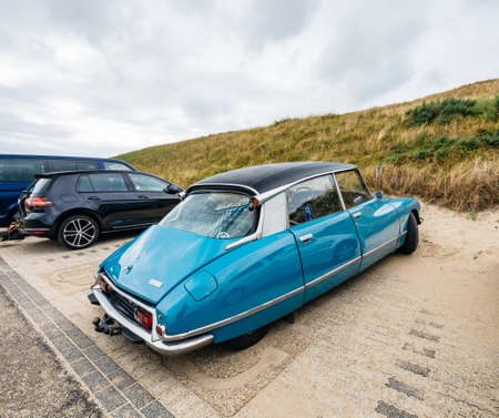 Overveen, Netherlands - Aug 16, 2019: Side view of luxury vintage old blue Citroen D Special limousine parked in the sand covered Dutch paid parking