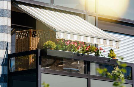 Französischer Balkon mit schöner Markise und mit Sonnenstrahlen bedeckten Blumen - Schutz bei Hitze und Strahlung Standard-Bild