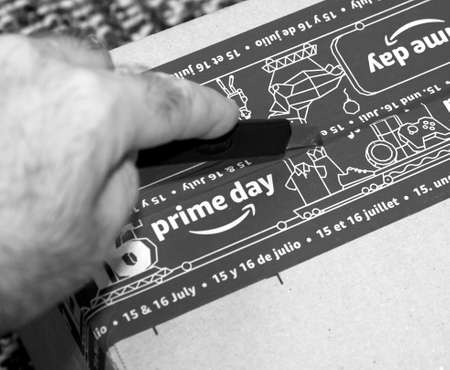 PARIS, FRANCE - JUL 4 2109: Man hand unpacking new Amazon Prime Day cardboard parcel with special blue tape for the Prime Day - black and white image Editorial