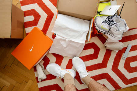 Paris France - Jul 13 2019: View from above of man measuring new Nike Epic React Flyknit 2 running shoes equipment on the living room manufactured by Nike sportswear