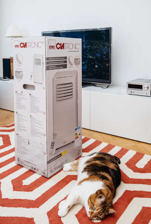 Paris, France - Jun 23, 2019: Cat near new portable air conditioner unit AC during hot summer in his living room Clatronic Editorial