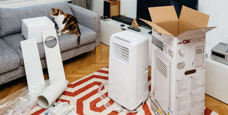 Paris, France - Jun 23, 2019: Curious cat inspecting the unboxing installing new portable air conditioner unit AC during hot summer in living room Clatronic model