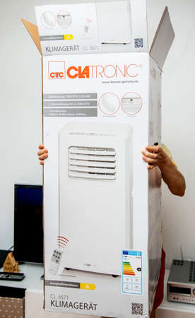Paris, France - Jun 23, 2019: Young man holding unboxing installing new portable air conditioner unit AC during hot summer in his living room Clatronic