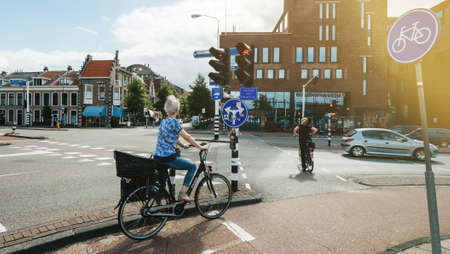 Haarlem, Netherlands - Aug 16, 2018: Side view of elegant Dutch woman waiting for green light riding a city bicycle - bike blue sign