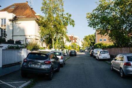 Strasbourg, France - Jul 29, 2018: Typical French street with buildings and cars in the background early in the summer - perspective view Editorial