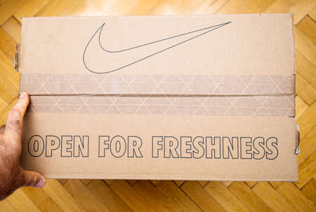Paris France - Jul 7 2019: Man hand hodling unboxing unpacking sport running shoes equipment manufactured by Nike sportswear - open for freshness and icon of the brand Editorial
