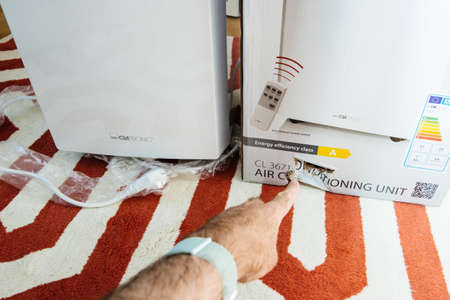 Paris, France - Jun 23, 2019: Young man unboxing installing new portable air conditioner unit AC during hot summer in his living room pointing with the finger to the damaged box during transportation