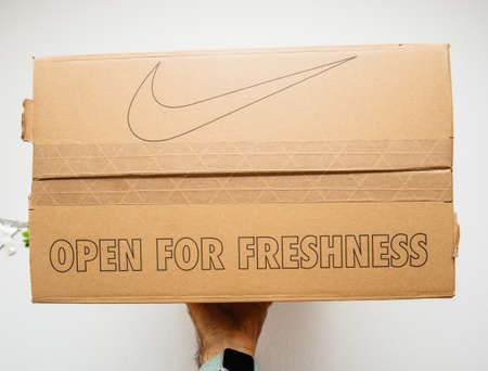 Paris France - Jul 7 2019: Man hand Above view unboxing unpacking sport running shoes equipment manufactured by Nike sportswear isolated on white background - open for freshness