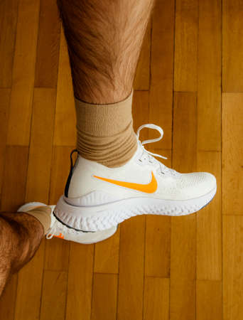 Paris France - Jul 13 2019: Man measuring new Nike Epic React Flyknit 2 running shoes equipment on the living room wooden floor manufactured by Nike sportswear showing white icon on side of the shoe Editorial