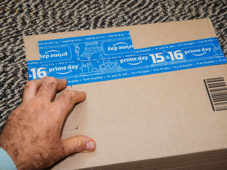 PARIS, FRANCE - JUL 4 2109: Man hand preparing to unbox unpacking new Amazon Prime Day cardboard parcel with special blue tape for the Prime Day Redactioneel