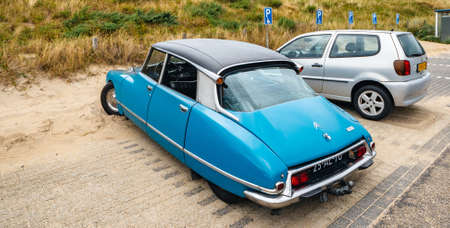 Overveen, Netherlands - Aug 16, 2019: Luxury vintage old blue Citroen D Special limousine parked in the sand covered Dutch paid parking - vertical image