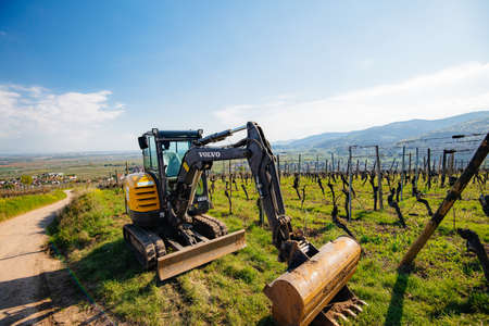 Alsace, France - Apr 19, 2019: Front view of a new modern Volvo Ec27C Compact excavator parked in vineyard