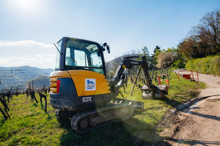 Alsace, France - Apr 19, 2019: Rear view of a new modern Volvo Ec27C Compact excavator parked in vineyard