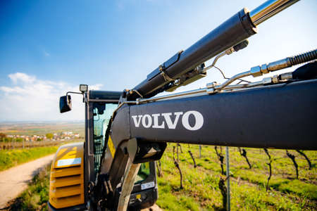 Alsace, France - Apr 19, 2019: View of a new modern Volvo Ec27C Compact excavator parked in vineyard with focus on the Volvo icon on the hydraulic arm Sajtókép