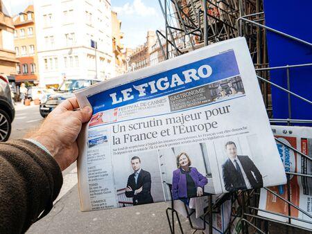 Strasbourg, France - May 25, 2019: Man hand POV reading at press kiosk Le Figaro newspaper featuring 2019 European Parliament pictures of Jordan Bardella Nathalie Loiseau, Francois-Xavier Bellamy