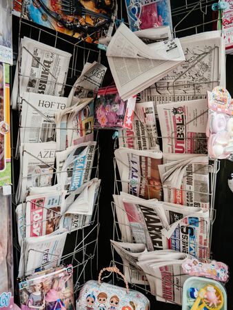 Baku, Azerbaijan - May 3, 2019: Row of multiple fresh newspapers at the press kiosk in central Baku with news about the President Ilham Aliyev - Azeri and Russian Press
