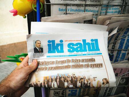 Baku, Azerbaijan - May 3, 2019: man hand buy shop for fresh newspaper Iki Sahil at the press kiosk in central Baku with news about the President Ilham Aliyev Redakční