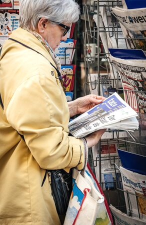 Strasbourg, France - May 25, 2019: woman reading German TAZ newspaper at press kiosk featuring 2019 European Parliament election predictions a day before the vote Redakční