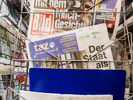 Strasbourg, France - May 25, 2019: Man hand POV reading TAZ at press kiosk newspaper featuring EU news and title der Staat als Beute Redakční