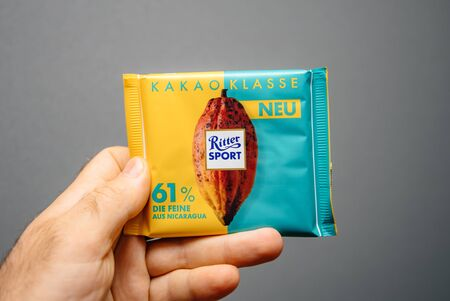 Paris, France - Apr 27, 2019: Man hand holding delicious Ritter Sport Cacao Classe with 61 percent chocolate against gray background