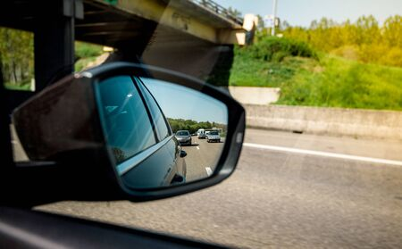 Rear view mirror of a car with multiple cars on a French highway