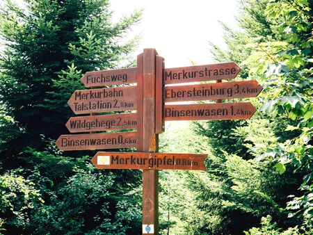 Multiple hiking routes distance and arrows on wooden pole in Black Forest near baden-Baden with Merkur Gipfel main arrow Imagens