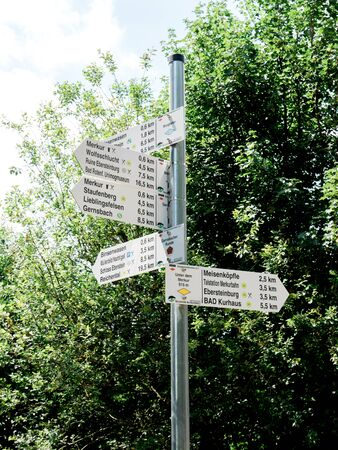 Multiple hiking routes distance and arrows on metal pole in Black Forest near baden-Baden Imagens