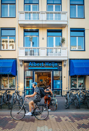 Haarlem, Netherlands - Aug 26, 2019: View of large Albert Heijn supermarket with male cyclist in front of the building