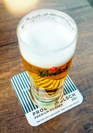 Overveen, Netherlands, - Aug 23, 2019: Vertical image of fresh Grolsch beer at Parnassia Cafe - Grolsch is Dutch brewery founded in 1615 by Willem Neerfeldt in Groenlo Editorial
