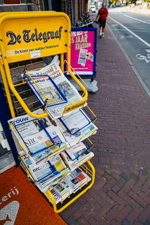 Haarlem, Netherlands - Aug 26, 2019: De Telegraaf newspaper stand on a Dutch street with Trouw, NRC Next, and other Dutch press with pedestrian silhouette in background