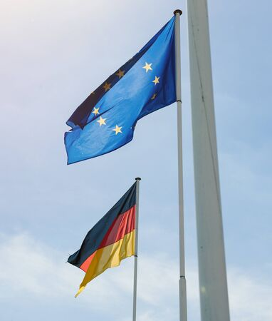 German and European Union flags waving with clear blue sky in the background at the border between France and Germany Stock Photo