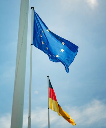 German and European Union flags waving with clear blue sky in the background