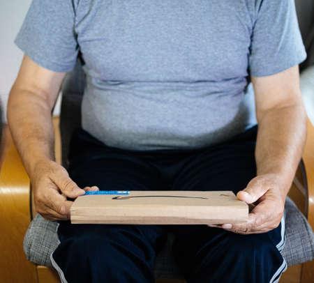 Paris, France - May 22, 2019: Senior man preparing to unbox cardboard box dispatched by Amazon online retailer