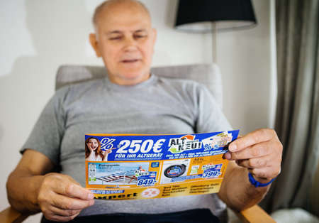 Paris, France - May 22, 2019: Senior man holding flyer advertising featuring on the cover Panasonic TV and AEG washing machine offered by Expert Oehler