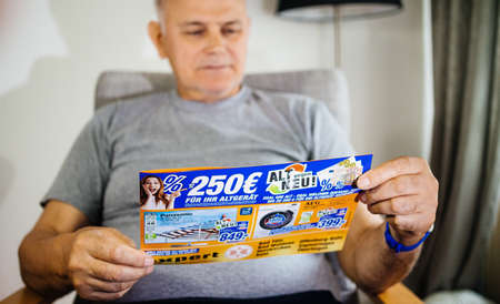 Paris, France - May 22, 2019: Senior serious man holding flyer advertising featuring on the cover multiple household products offered by Expert Oehler - 4k TV sets , washing machines 新闻类图片