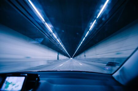 Perspective view fron the car at the long blue tunnel with end at the end