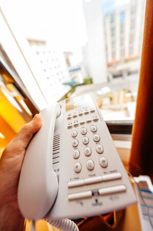 Man hand holding old vintage keypad telephone in hand in hotel room - focus on the phones keypad