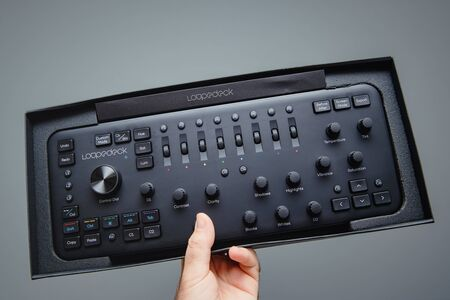 Paris, France - Sep 20, 2019: Man hand holding against gray background new Loupedeck Plus photo and video editing console