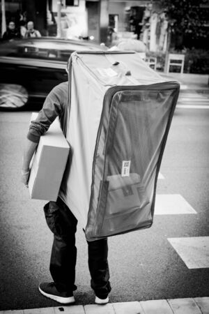 Barcelona, Spain - Nov 17, 2017: Black and white image rear view delivery man holding a carton box in hand and carrying extra-large see-through net delivery bag on his back with Amazon parcels